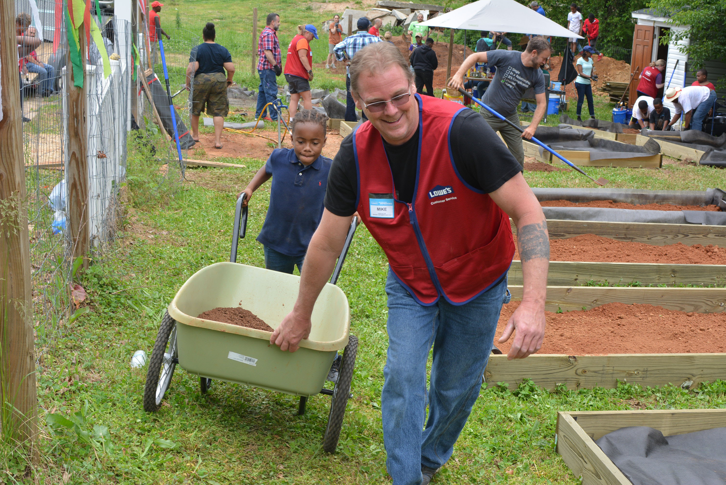 Lowe's employee and boy with wheelbarrow